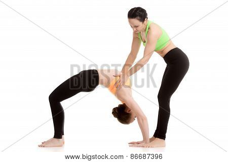 Instructor Assists Student In Urdhva Dhanurasana Yoga Pose