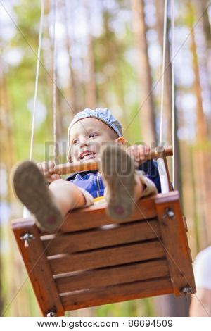 Portrait Of Little Cute Caucasian Boy On Swing