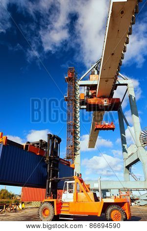 Orange Forklift And Crane At Loading And Unloading Of Cargo In The Port