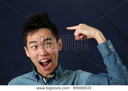 Funny young Asian man pointing the index finger at his haircut