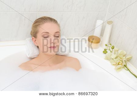 Young Woman Lying In Bath With Foam