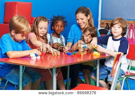 Children and nursery teacher playing with building blocks in a kindergarten