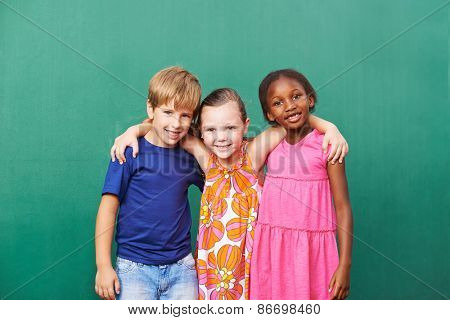 Three happy friends embracing in kindergarten in front of a green wall