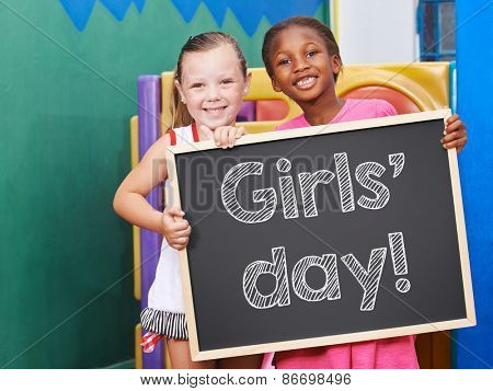 Two happy children holding a blackboard for the Girls' Day