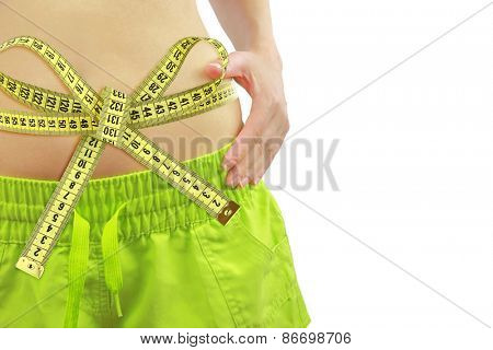 Woman's fit belly with measuring tape, isolated on white