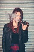 stock photo of exhale  - Trendy young woman puffing on an e - JPG