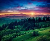 stock photo of breathtaking  - Green hills glowing by warm sunlight at twilight - JPG