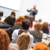 image of speaker  - Speaker giving presentation in lecture hall at university - JPG