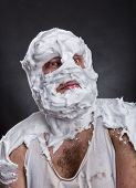 foto of shaved head  - Bizarre man with face completely in shaving foam thinks over grey - JPG