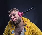 image of plunger  - Strange man in a terry bathrobe with a plunger in his ear  - JPG