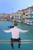 foto of girder  - Businessman sitting on light metal girder beam with view of Venice - JPG