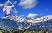 picture of archery  - Businessman practicing archery with mountain valley in foreground - JPG