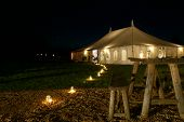 stock photo of tent  - Exterior of wedding marquee tent at night with lit tea lights - JPG