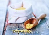 picture of millet  - raw millet in wooden spoon and on a table - JPG
