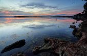 picture of shoreline  - Mirrored reflections on the tranquil waters of St Georges Basin from the banks at Wrights Beach. Soft dusk hues of red orange and blues fill the scene and contrast against the rocky shoreline. ** Note: Soft Focus at 100%, best at smaller sizes - JPG
