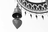 foto of windchime  - brass bell hanging from traditional metal umbrella black and white - JPG