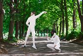 stock photo of rapier  - Two rapier fencer women fighting over park alley - JPG