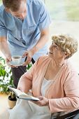 picture of disability  - Picture of caregiver helping disabled female pensioner - JPG