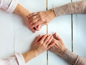pic of granddaughters  - Unrecognizable grandmother and her granddaughter holding hands - JPG