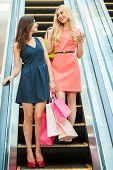 image of escalator  - Two girls standing on escalator and carrying shopping bags - JPG