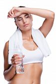 pic of forehead  - Tired young woman holding bottle with water and touching her forehead with hand while standing isolated on white - JPG