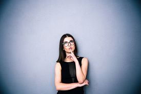 foto of shhh  - Young charming woman in glasses with finger over lips standing over gray background - JPG