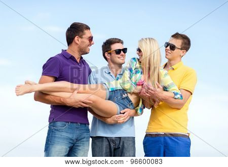 summer, holidays, vacation, happy people concept - group of friends having fun and carrying girl on hands at beach