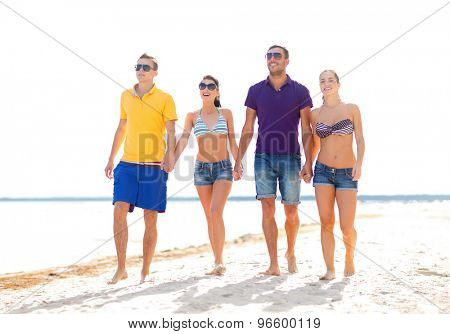 summer holidays, vacation, tourism, travel and people concept - group of happy friends holding hands and walking along beach