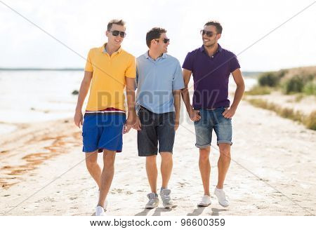friendship, summer vacation, holidays and people concept - group of smiling male friends in sunglasses walking along beach