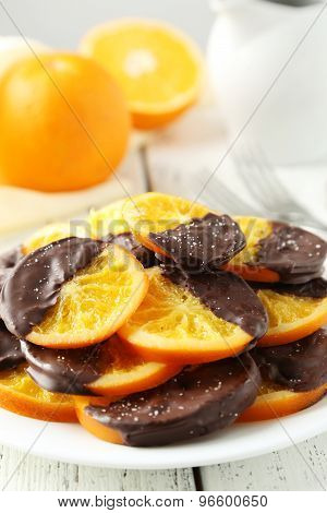 Delicious slices of orange coated chocolate on plate on white wooden background