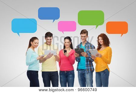 friendship, technology, communication and people concept - group of smiling teenagers with smartphones and tablet pc computers over messenger text bubbles and gray background