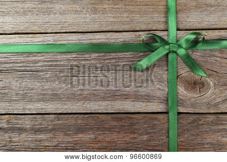 Green ribbon with bow on grey wooden background