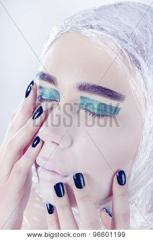 Petty woman wrapped in cellophane looking forward standing on light grey background