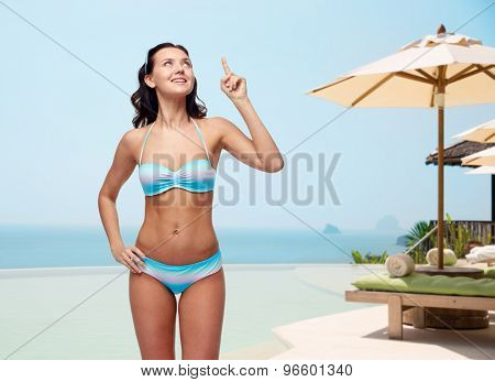 people, travel, swimwear, summer and beach concept - happy young woman in bikini swimsuit pointing finger and looking up to something imaginary over infinity edge pool at hotel resort background