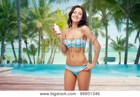people, skincare, tanning, summer and travel concept - happy young woman in bikini swimsuit holding sunscreen bottle over tropical beach with palm trees and pool at hotel resort background