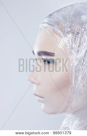 pretty woman wrapped in cellophane looking forward standing on light grey backg