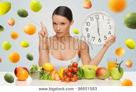 people, eating and diet concept - woman with healthy food holding big clock, pointing finger up and warning over gray background with falling fruits