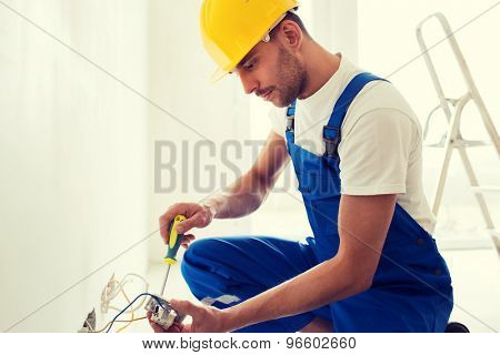 building, renovation, technology, electricity and people concept - builder with screwdriver fixing socket indoors