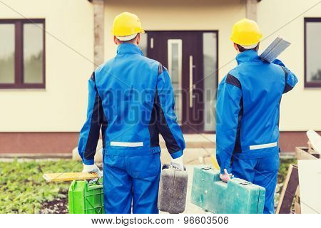 business, building, teamwork and people concept - group of builders in hardhats with toolboxes outdoors