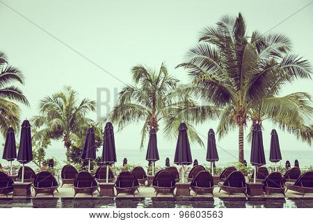Poolside with chairs and palm trees ( Filtered image processed vintage effect. )