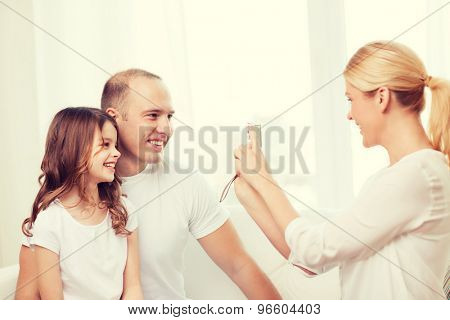family, child, photography and home concept - smiling happy mother taking picture of father and daughter