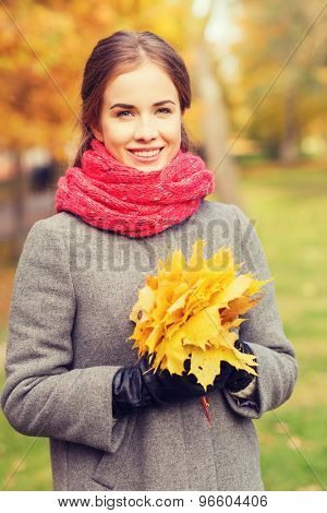 happiness, season and people concept - smiling woman with bunch of leaves in autumn park