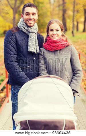 love, parenthood, family, season and people concept - smiling couple with baby pram in autumn park