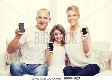 family, child, technology and home concept - smiling parents and little girl with blank black screen smartphones at home