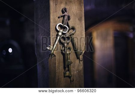 old keys on a column, antique wood background