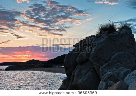 Silhouette of sea rocks and reflection of cloudscape at sunset