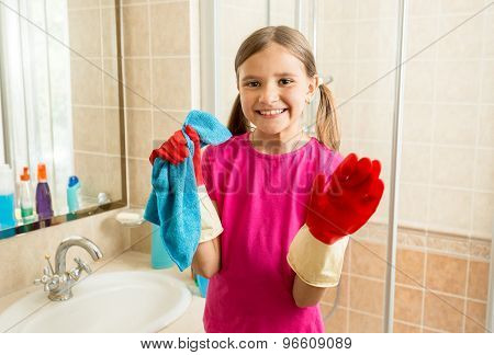 Portrait Of Cute Girl In Rubber Gloves Doing Cleanup At Bathroom