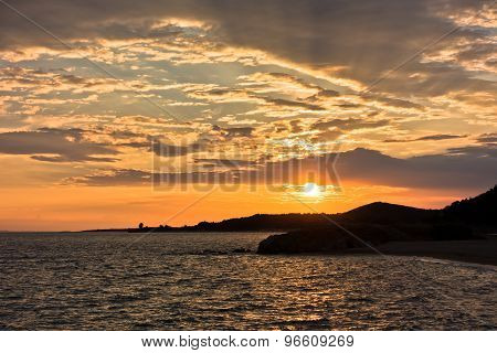 Picturesque cloudscape with silhouette of a sea rocks at sunset