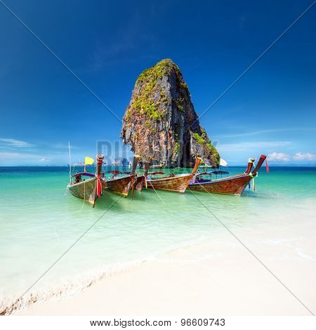 Travel photography of wooden boats on shore of tropical sea with scenic rock mountain in water. Vacation journey background of Thailand nature