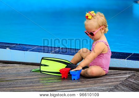 cute girl with flippers in swimming pool at beach